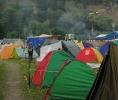 В правом верхнем углу видно, как вереница людей спускается вниз с горы и расползается в многочисленные палатки
